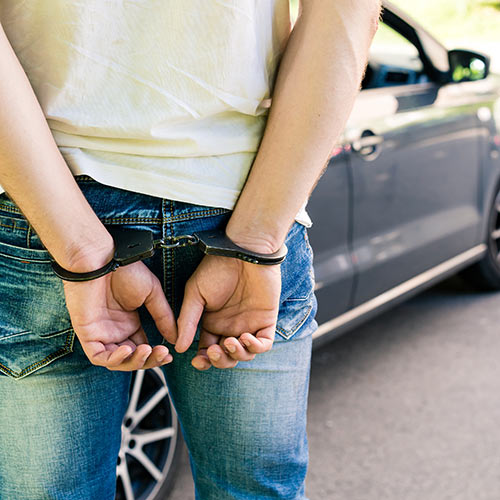 Felony DUI Charges Defense Tampa, Florida. Person in handcuffs near a car.
